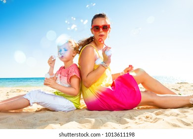 Colorful and wonderfully cheerful mood. happy trendy mother and child in colorful clothes on the seashore blowing bubbles