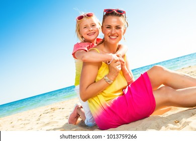 Colorful and wonderfully cheerful mood. happy modern mother and daughter in colorful clothes sitting on the seacoast