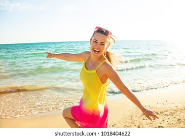 Colorful and wonderfully cheerful mood. happy modern woman in colorful dress on the seashore in the evening having fun time