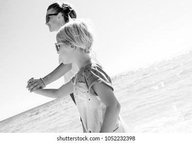 Colorful and wonderfully cheerful mood. happy modern mother and child in colorful clothes on the seashore walking