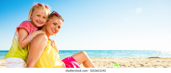 Colorful and wonderfully cheerful mood. Portrait of smiling trendy mother and daughter in colorful clothes on the seashore