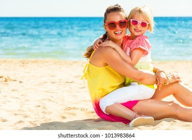 Colorful and wonderfully cheerful mood. Portrait of happy modern mother and child in colorful clothes sitting on the beach