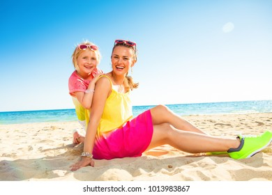 Colorful and wonderfully cheerful mood. Portrait of happy trendy mother and daughter in colorful clothes on the seashore