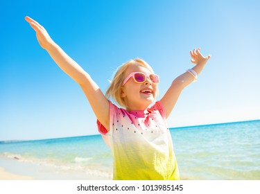 Colorful and wonderfully cheerful mood. Portrait of happy trendy child in colorful shirt on the seacoast rejoicing