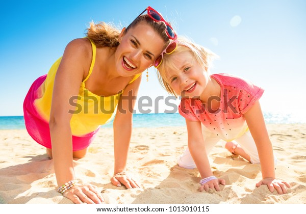Colorful and wonderfully cheerful mood. Portrait of happy trendy mother and daughter in colorful clothes on the beach