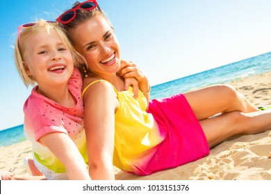 Colorful and wonderfully cheerful mood. smiling trendy mother and daughter in colorful clothes on the seashore