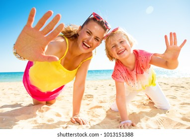 Colorful and wonderfully cheerful mood. smiling modern mother and child in colorful clothes on the seashore showing palms