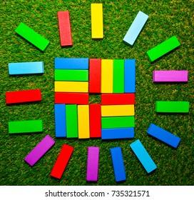 colorful wood block on green grass , sun shape.