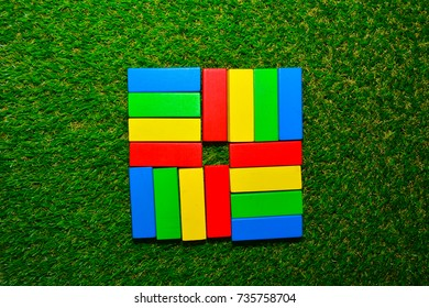 colorful wood block on green grass. square shape with red plus sign in center.