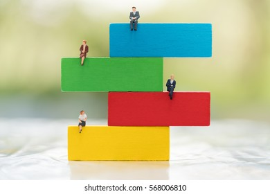Colorful wood blocks stack game with miniature people , playing and learning background concept