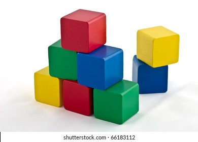 Colorful wood building blocks stacked as pyramid. Isolated on white