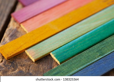 Colorful wood stain color test samples, on rough wood. Shallow depth of field.