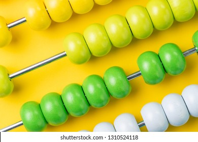 Colorful wooden abacus beads on yellow background, business financial or accounting cost and expense calculation concept, or use in education school arithmetic symbol.