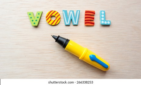 Colorful wooden alphabet letter set with cute pen and text VOWEL. Concept of fun preschool or back to school. Shot with natural light. Slightly defocused and close-up shot. Copy space.