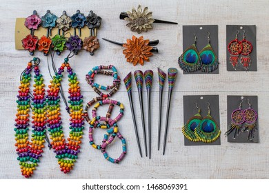 Colorful wooden beads necklace, bracelets, hairpins and earrings on white wooden background, close up, top view