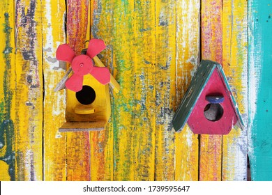 colorful wooden bird house on grunge wooden panel wall