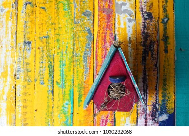 colorful wooden birdhouse with grunge wooden panel background.