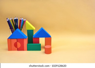 Colorful wooden block houses and glass cup with pencils