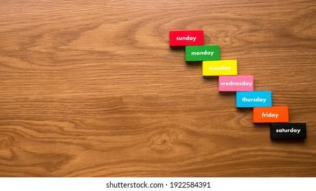 A colorful wooden block in stair shape with text of days of the week on wooden background with copy space.