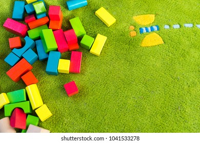 Colorful wooden blocks for children on green carpet, top view