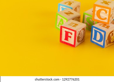 Colorful wooden blocks with letters on a yellow color background
