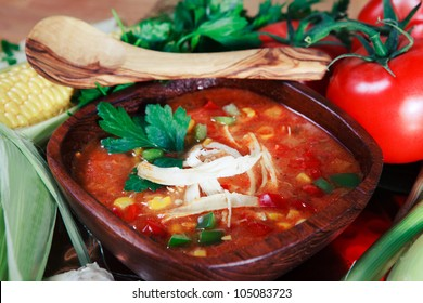 Colorful wooden bowl of Chicken Tortilla Soup with the fresh ingredients deconstructed around the serving.