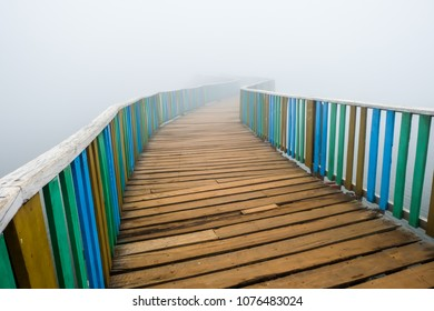 Colorful wooden bridge over lake on a misty day; Loimwe, Myanmar