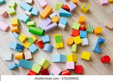 Colorful wooden building blocks on floor children room. Selective focus