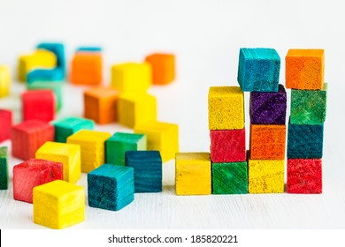 Colorful wooden building blocks on white table. Selective focus