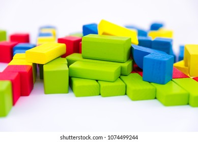 Colorful wooden building toy blocks isolated on a white background