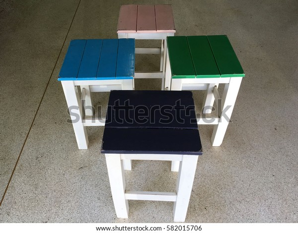 Colorful wooden chairs on cement floor