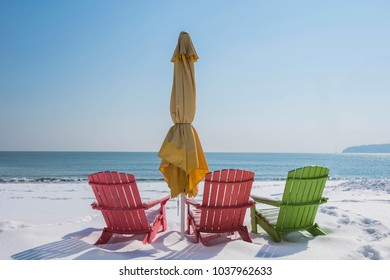 Colorful wooden chairs on a snowy beach