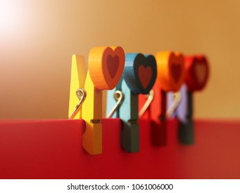 colorful wooden clothespin on a pink paper, set