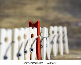 colorful wooden clothespin - selective focus, standing out from the crowd, leadership, difference concept. toned image