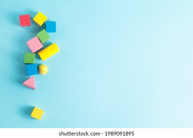 Colorful wooden geometric figures on blue background with free copy space for text