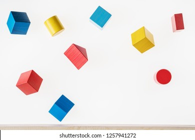 Colorful wooden geometric shapes are floating. Concept of creative, logical thinking. Abstract geometric real floating wooden blocks.