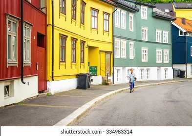 Colorful wooden house architecture and a young tourist on a bike in Oslo, Scandinavia