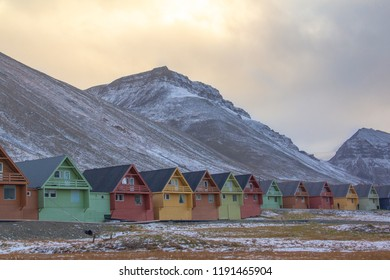 Colorful wooden houses in red, yellow, and green, beneath a fall / autumn sky by the mountains on one side of the valley in Longyearbyen, Spitsbergen, Svalbard, Norway.