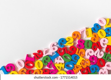 Colorful wooden numbers on part of background with copy space. Numbers texture abstraction on part of board. Top view of multicolor numbers from zero to nine. Mathematic topic. Back to school concept