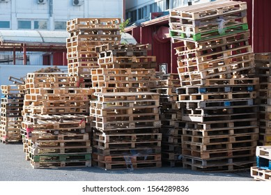 Lot of colorful wooden pallets on the pile in front of the factory