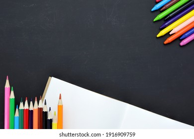 colorful wooden pencils, notepads on a blank black chalk board, school stationery, Top view with copy space. Back to school concept.