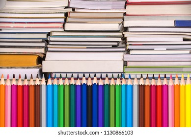 Colorful wooden pencils and piles of books, back to school background concept