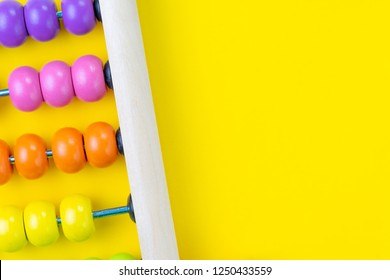 Colorful wooden pink and orange abacus beads on yellow background with copy space for presentation, business financial or accounting profit and loss concept, or use in education school arithmetic.