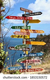 Colorful wooden sign with the names of landmarks and distances in Rumah Pohon Molenteng view point, one of the most amazing spots in Nusa Penida Island, Bali, Indonesia.