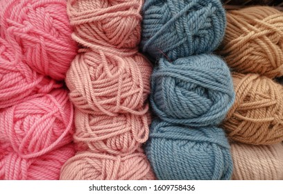 Colorful woolen balls of yarn. Background of colored yarn balls. Needlework. Knitting. Hobbies and leisure. Balls of yarn in pink, blue-grey, salmon and tan colors.