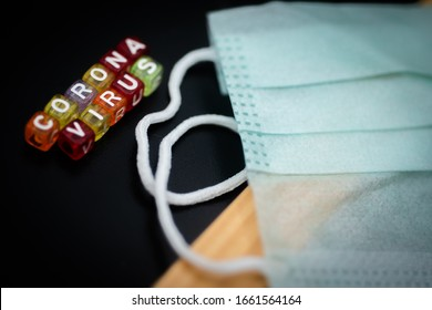 Colorful word CORONA VIRUS english alphabet cube on black color background and face mask , selective focus