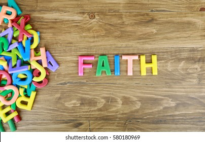 """The colorful word """"FAITH"""" next to a pile of other letters over the old wood board"""