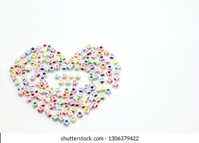 Colorful word love you made from alphabet cube beads surround with heart shape on white background. Love and happy valentine's day concept