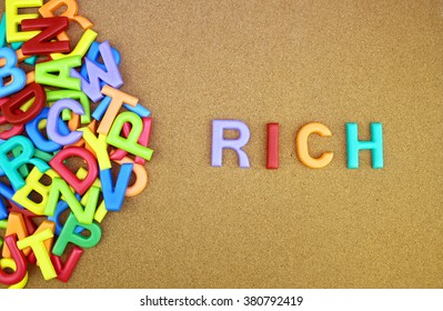 "The colorful word ""RICH"" next to a pile of other letters over the brown board surface composition."