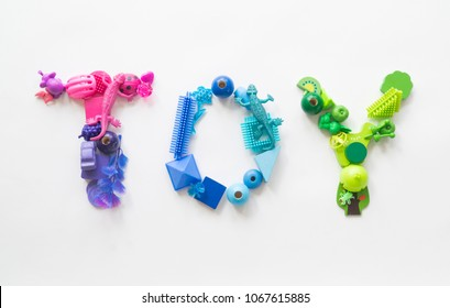 "Colorful word ""TOY"" of toys on a white background. Lots of kids games. Rainbow color Ombre transition."